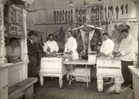 Interieur van een slagerij in Amsterdam, met links de eigenaar in net pak en personeel in witte jassen dat karkassen vlees uitbeent. Achter ...