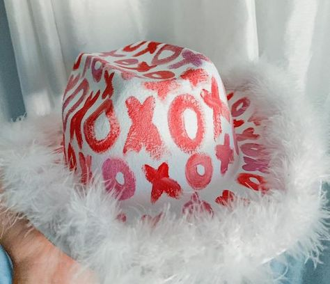 Xoxo Cowboy Party Hat. This hat is great for parties, games, and trendy photos. This item is handmade so each one is unique. No returns are allowed. This is an adult sized cowboy hat. Pink, Purple, and Red x's and o's are painted all over the hat in random orders. Hat has white marabou boa around edges with a rhinestone strip around the center of hat. Hat is a white cowboy hat. Dimesnsions are 22 inches inside and 26 inches for outside brim. I hope you LOVE your cowboy hat!! 😌😊Love, Eminence ⚡ Cowgirl Costume, Cowgirl Party, White Cowboy Hat, Diy Hat, Girl With Hat, Birthday Fun, Party Hats, Preppy, Halloween Costumes