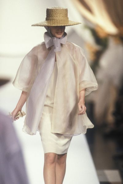 Straw Fedora, a nude off-white Chiffon layered cape held together by a large bow extending from the high neck with length Voluminous statement sleeves over a narrow skirt in the same colour by Christian Dior, Spring-Summer Couture