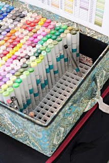 A plastic ceiling tile meant to cover fluorescent lights, cut down and inserted into a box for organizing and carrying copic markers.