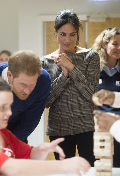 Prince Harry and his fiancee Meghan Markle watch a game of Jenga during their visit to Star Hub.