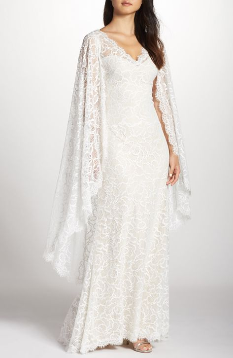 Fluttery panels draped from the shoulders of this intricate eyelash-lace gown impart ethereal bohemian romance. Style Name:Tadashi Shoji Cape Detail Lace Gown. Style Number: 5699719. Available in stores.