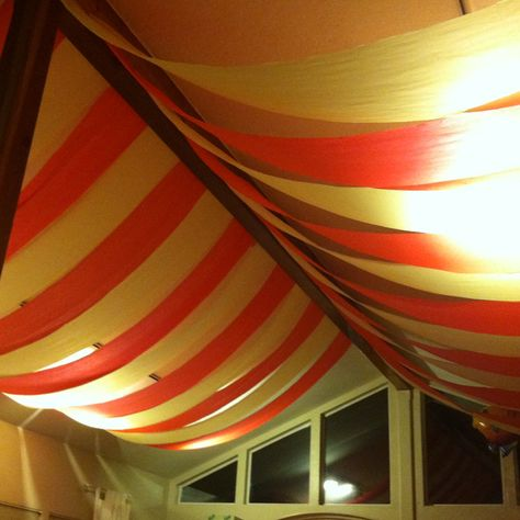 DIY circus tent ceiling for themed party Made with table cloths from the dollar store cut into thinner strips