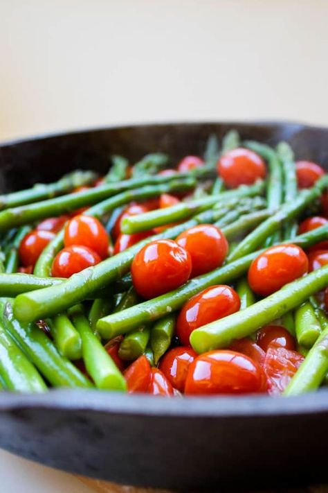 Sautéed Asparagus and Cherry Tomatoes by The Food Charlatan. This simple sautéed asparagus is paired beautifully with bright cherry tomatoes. A splash of cream and Parmesan rounds everything out. If you don't know how to sauté asparagus, it's easy! It's great year-round as a summer side dish or a perfect compliment for a holiday meal. #asparagus #cherrytomatoes #easy #healthy #parmesan #sidedish #holiday #sauteed #butter #simplerecipe #christmas #easter #thanksgiving #summer #cream