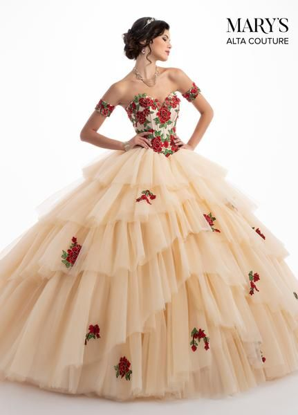 Make a grand entrance in this floral appliqued strapless ball gown with A-line skirt by Mary's Bridal Alta Couture Collection MQ3028 during your Quinceanera, Sweet 16, or at any formal event. Diaphanous tulle gown with a strapless sweetheart neckline, detachable arm cuffs, exposed boning, and contrast floral appliques. The gown finishes with a lace-up back closure, shredded tulle skirt, full train, and a matching tulle cape. Colors: Dark Champagne/Red, White/Pink Sizes: 0-20, 20W-30W Fabric: ...