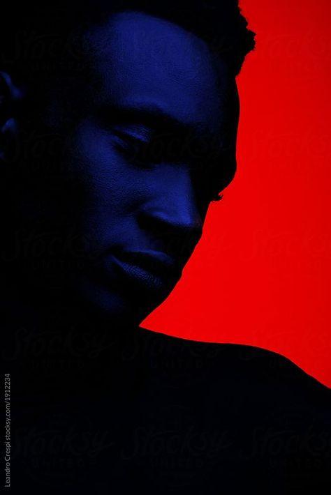 Creative dark portrait under blue light over red background. by Leandro Crespi for Stocksy United