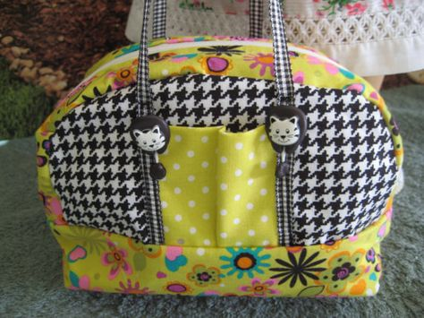 """Sport bag for an 18"""" doll, with zippered top opening, grosgrain straps, two outside pockets and decorative button trim."""