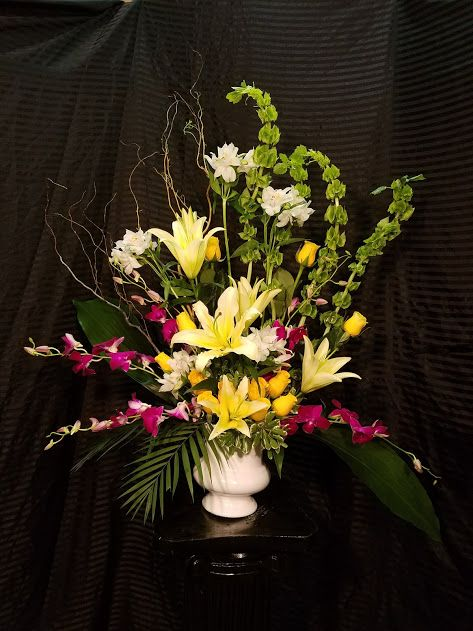 Centerpiece With Orchids Ti Leaves Lilies Alstroemeria Yellow Roses And Bells Of Ireland Event Flowers Yellow Roses Sympathy Arrangements