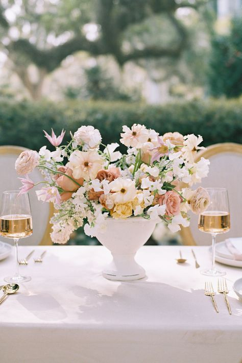 From the editorial Sunset on the Seine by Claude Monet Inspired This Spring Wedding Editorial's Color Palette. The mix of warm and cool pastel tones played out so beautifully in Moonstruck Florals' arrangements.  Photography: @lisasilvaphotography  #floralarrangements #weddingflowers #weddingfloraldesign #weddingreceptiontable
