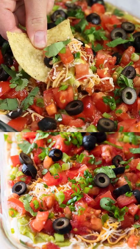 7 Layer Dip Recipe - Layers of salsa, guacamole, sour cream, beans, cheese, pico de gallo and olives. The perfect appetizer for game day or a friends get-together. People will gather around this layered taco dip until it's gone! #appetizers #mexicanfoodrecipes #mexicanfood #easyrecipe #recipes #recipevideo #foodvideos #videos #iheartnaptime