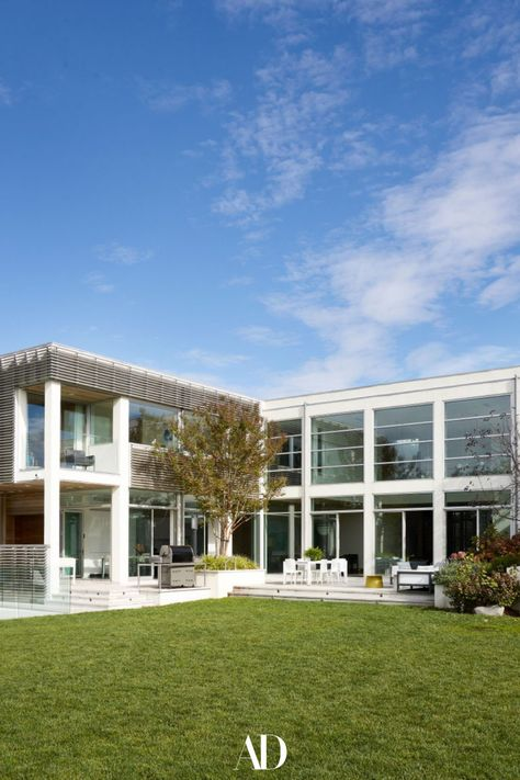 Interior designer Bella Mancini worked with Douglas Wright Architects to craft a contemporary dream home not far from Manhattan. The Corbusier-inspired facade was designed by Douglas Wright Architects. #facade #house #mansion #curbappeal #design #grass #glass #windows #outdoors #landscaping #architecture