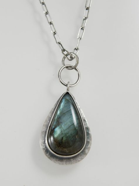 Labradorite cabochon, set in sterling silver. The sterling has been oxidized and brushed to a satin finish. The sterling flat drawn chain is.