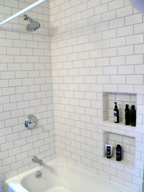White subway tiles in bath surround - love little shelves, but would use mosaic colors in the shelves.