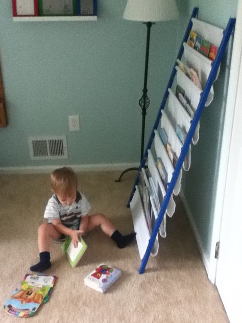 Use side of old crib, turn on its side, to make a sling bookshelf for children's books! Awesome idea.
