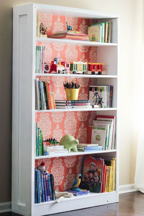 Awesome (and easy!) bookshelf makeover using paint and removable wallpaper.