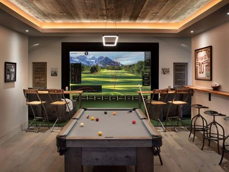 Having a golf simulator, pool desk and reclining chairs, this particular modern game room certainly puts the man give to shame. com to see even more of the space, with a reclaimed wood ceiling. Man Cave Garage, Garage Game Rooms, Game Room Basement, Basement Man Caves, Game Room Bar, Garage Bar, Golf Man Cave, Man Cave Games, Bar Design