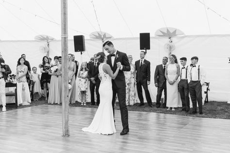 Amazing black and white photo of our gorgeous bride & groom enjoying one another during their first dance as their parents and bridal party watched on.  #Couple #Wedding #FirstDance #Dancing #Suit #WeddingDress #Sheath #Bride #Groom #BlackAndWhite #Black #White #DanceFloor #SailclothTent #TentPole #Wood #Wooden #Suspenders #BridalParty