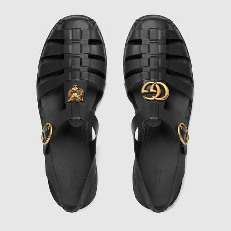 ace82c104 Shop the Rubber buckle strap sandal by Gucci. A strap sandal in rubber is  embellished with Double G hardware on one shoe and metal feline head on the  other.