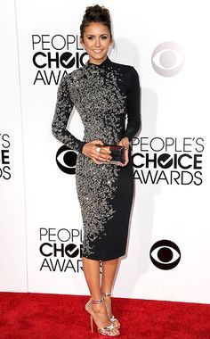 Nina Dobrev arrived at the 2014 People's Choice Awards looking impossibly elegant in a high-collar long-sleeve Jenny Packham cocktail dress with crystal embellishments, styling it with a Kara Ross ring, a metallic box clutch and silver strappy heels.