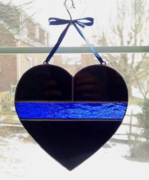 This stained glass heart suncatcher depicts the thin blue line in support of police and law enforcement. It measures 6 inches by 6 inches, and is made with black opalescent glass with a cobalt blue textured cathedral glass center line. It comes ready to hang with a blue ribbon and