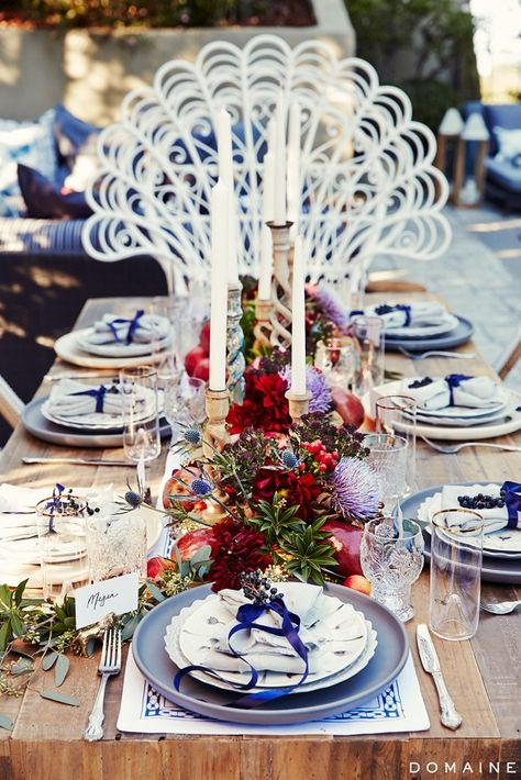 Wooden table with linen napkins, taper candles, flowers, greenery, and fruit as centerpiece.