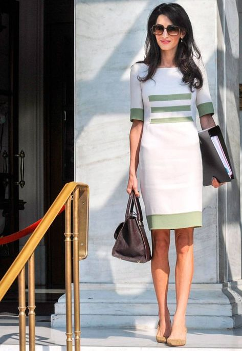Amal Clooney wears a green and white shift dress, nude pumps, a classic brown satchel, and ladylike sunglasses