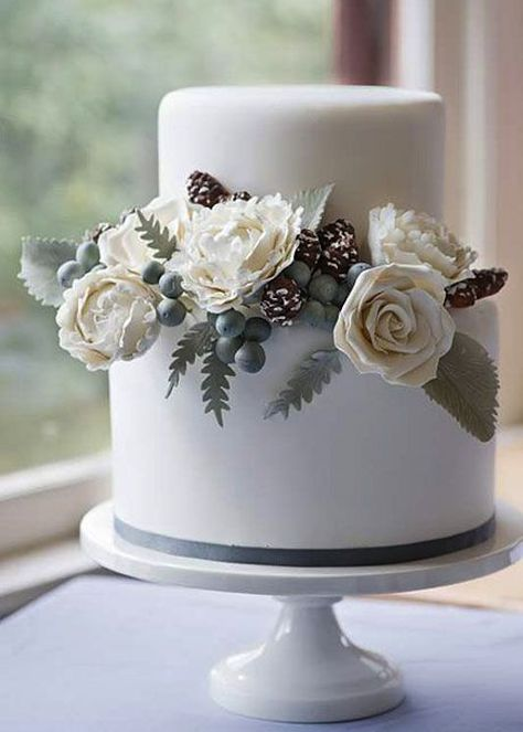 What a gorgeous winter wedding cake with roses, silver brunia berries and pinecones!