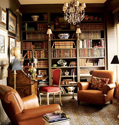 Room of the Day ~ sophisticated, cozy library - warm colors, animal print rug, comfortable chairs, chandelier, old books, antique desk.