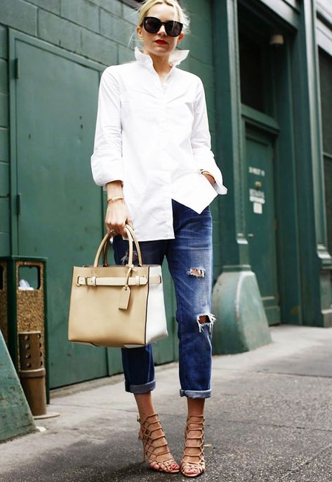Blair Eadie wears a crisp button-down shirt, boyfriend jeans, strappy heels, and a leather tote bag