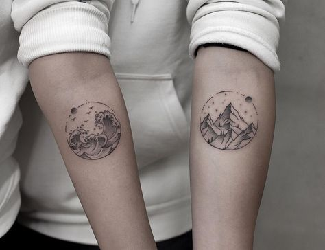 Matching circular scenes by Aki Wong tattooed on both forearms