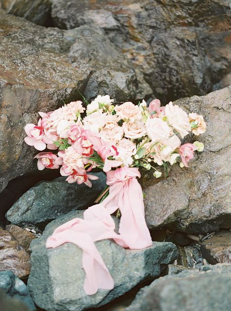 What is more romantic that an oversized organic bouquet for a dreamy seaside wedding. This couple took their photos in the tide pools of Sunset Cliffs in San Diego, CA. Brides bouquet was lush and ethereal with a soft blush and pink palette for Spring of roses, orchids and carnations. #orchidbouquet #springweddingflowers #beachwedding #sandiegobeachwedding #sandiegoweddingflorist #sunsetcliffssandiego