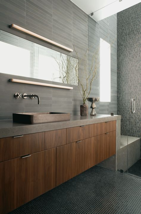 """ANN SACKS Luxor Grey 1-3/4"""" x 17"""" limestone field in honed finish with @Kallista Kelly Kelly Kelly Kelly Kelly Plumbing Trinidad decorative vessel in traditional bronze with One wall mount lavatory set in charcoal (designer: Jeff Andrews - Design, photographer: Grey Crawford)"""