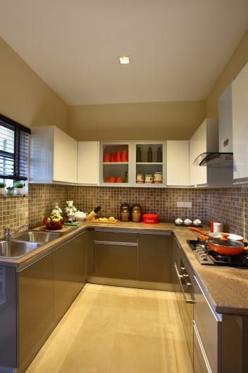Beige Color Modular Kitchen With Tiled Wall And Cabinets By Nikita