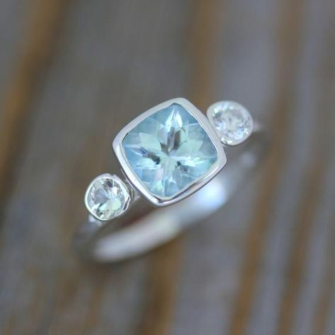 Beautiful 7mm cushion shaped Blue Aquamarine Gemstone. Birthstone of March Natural stone, ethically sourced Each Aquamarine is approximately 1.25 - 1.5 cts with variation in the depth of the gemstone. Flanked on either side by two 3.5mm white sapphires, bezel set into this Argentium