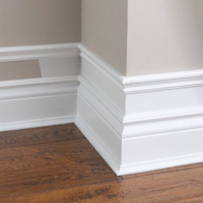 Create an Exaggerated Baseboard | Add small pieces of trim to the top of existing baseboard, add a few inches and add another piece of moulding. Paint the wall and trim white. Cheap Easy!!!