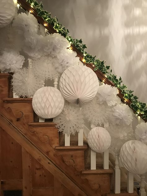 Our stairs and hallway at Christmas. Faux ivy, twinkly lights with white tissue honeycombs, pom poms and snowflakes.  #stairs #hallway #entranceh...