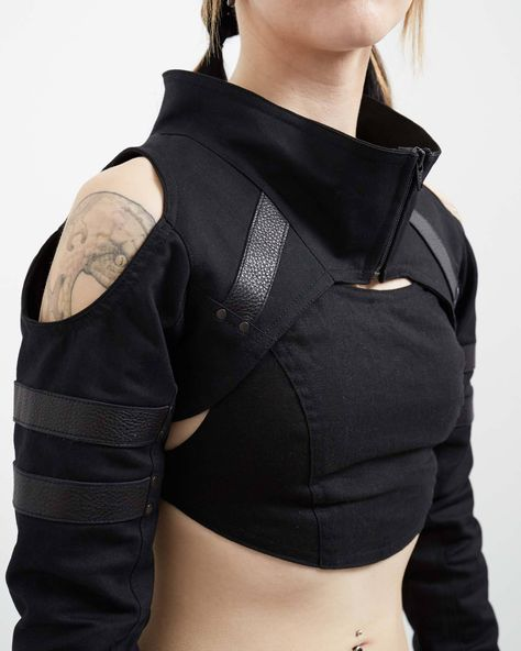 The Variant is our newest shrug, and designed to be as aggressively comfortable as it is stylish. Made with black stretch denim and accented with leather strapping, it features open shoulders and double cuffs for ease of movement and proper fit across all body sizes. For a fantastic layered look, try pairing this shrug with our Outlaw Cowl. Available in black. Each item is made to order, by hand. For more information on special sizing, please go here.