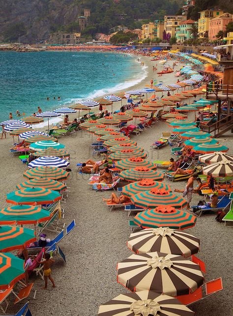 Umbrellas form a curved line on the beach in Monterosso, one of the five towns in Italy's Cinque Terre