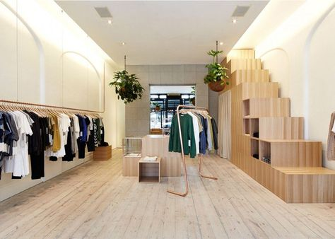 Garments in this retail interior by Australian design studio Sibling are displayed on copper clothes rails and stacked wooden cubes.