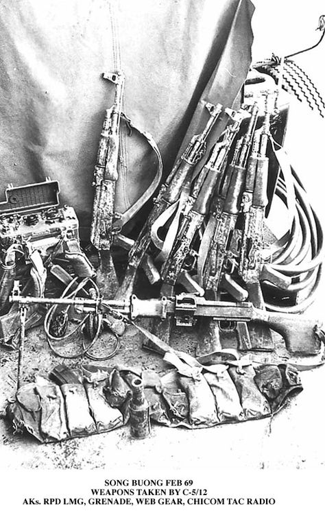 A captured Viet Cong weapons cache. There are several Type 56 Assault Rifles, as well as a few chest rigs, a Chicom grenade, and an RPD. There even appears to be a PRC-25 radio in the upper left corner.