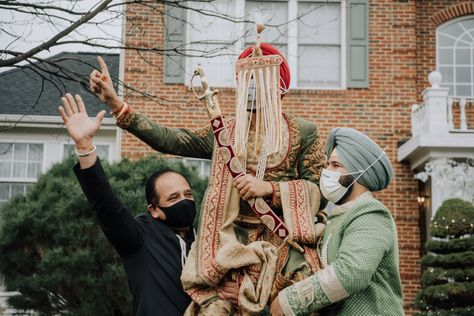 Family lifts Indian groom in the air in celebration. Photograph by Catch Motion Photography, VA #sehra #facecovering #covidwedding #indianwedding #sikhgroom #photography