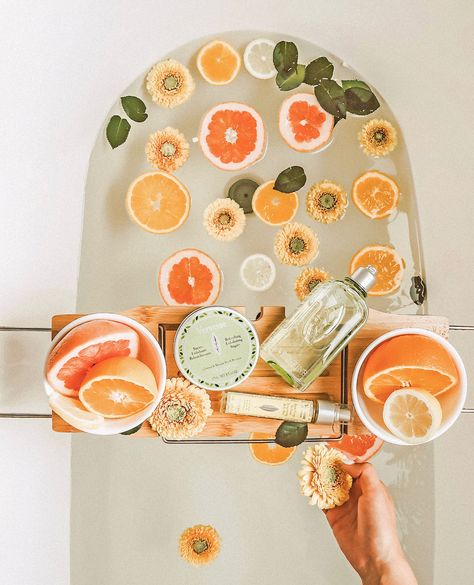 bathtub with citrus slices, flowers and leaves floating in it