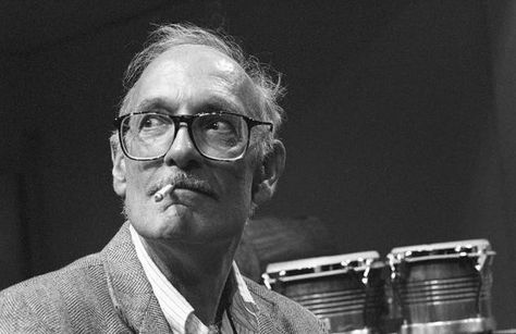 Composer George Crumb smoking a cigarette in front of some bongos