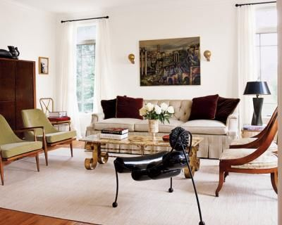 Eclectic Style A Tufted Sofa Is Paired With Vintage Cocktail Table Quirky Tripod Seat Modern Danish Armchairs And English Regency Bergeres