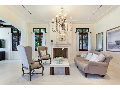 A living room with unique furniture and chandelier. Miami Beach, FL Coldwell Banker Residential Real Estate