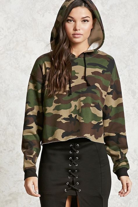 A soft knit boxy hoodie featuring an allover camo print, long sleeves, fleece lining, ribbed knit trim, and a raw-cut slightly cropped hem.