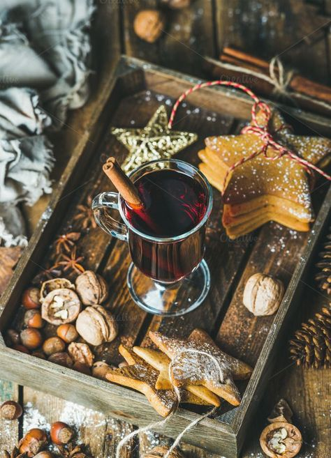 wine & gingerbread cookies Glass of mulled wine in wooden tray with Christmas decoration toys gingerbread cookies nuts cinnamon anise and pine cones over rustic wooden background selective focus vertical composition