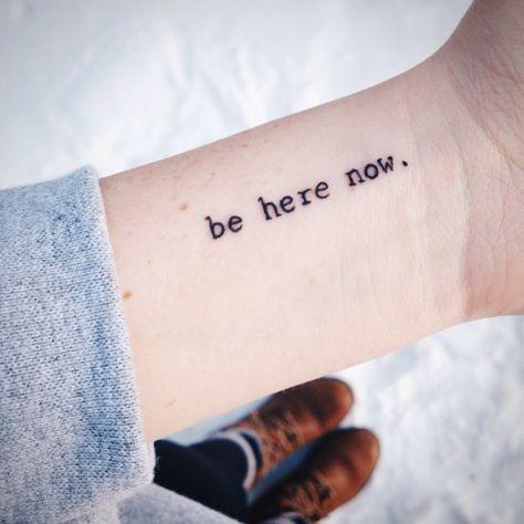 """Pequeño tatuaje que dice """"Be here now"""", frase en inglés que significa """"ahora estate aquí"""" en la muñeca de Ashley."""