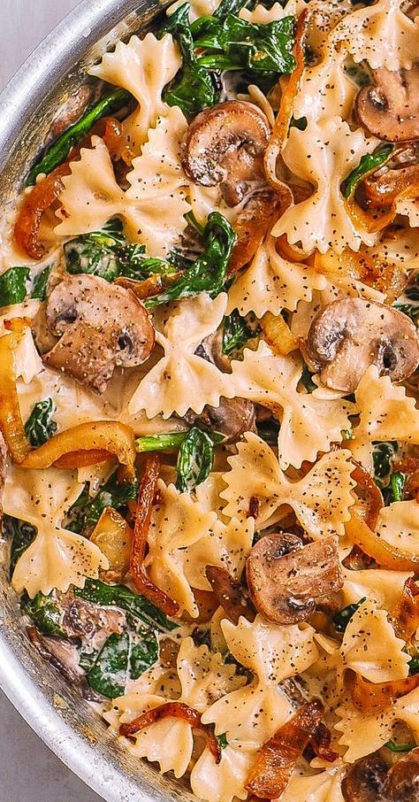 Creamy Bow Tie Pasta with Spinach, Mushrooms, and Caramelized Onions. This simple meatless Italian dinner is pure comfort food! The bow-tie shaped pasta is perfectly matched with rich and buttery Parmesan sauce! #bowtie #pasta #mushrooms #spinach #caramelizedonions #meatless #dinner #easyrecipe