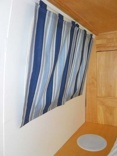 attach magnet strip on window sill, magnets inside curtain hems, stays closed at bottom of camper window!